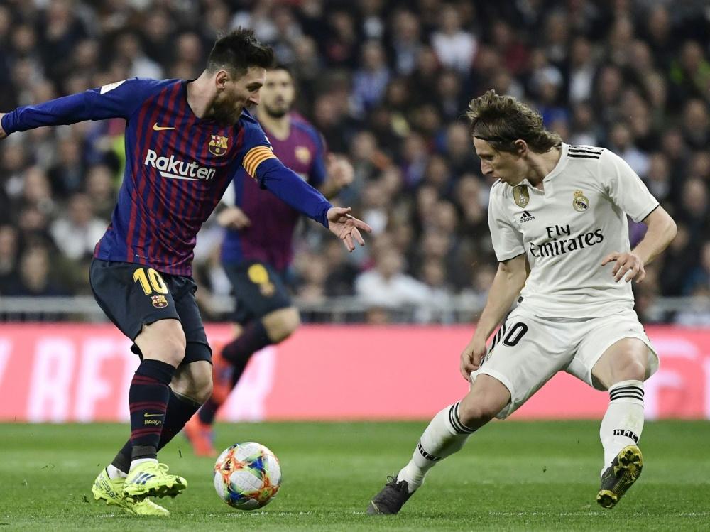 Lionel Messi (l.) im Duell mit Luka Modric. ©SID JAVIER SORIANO
